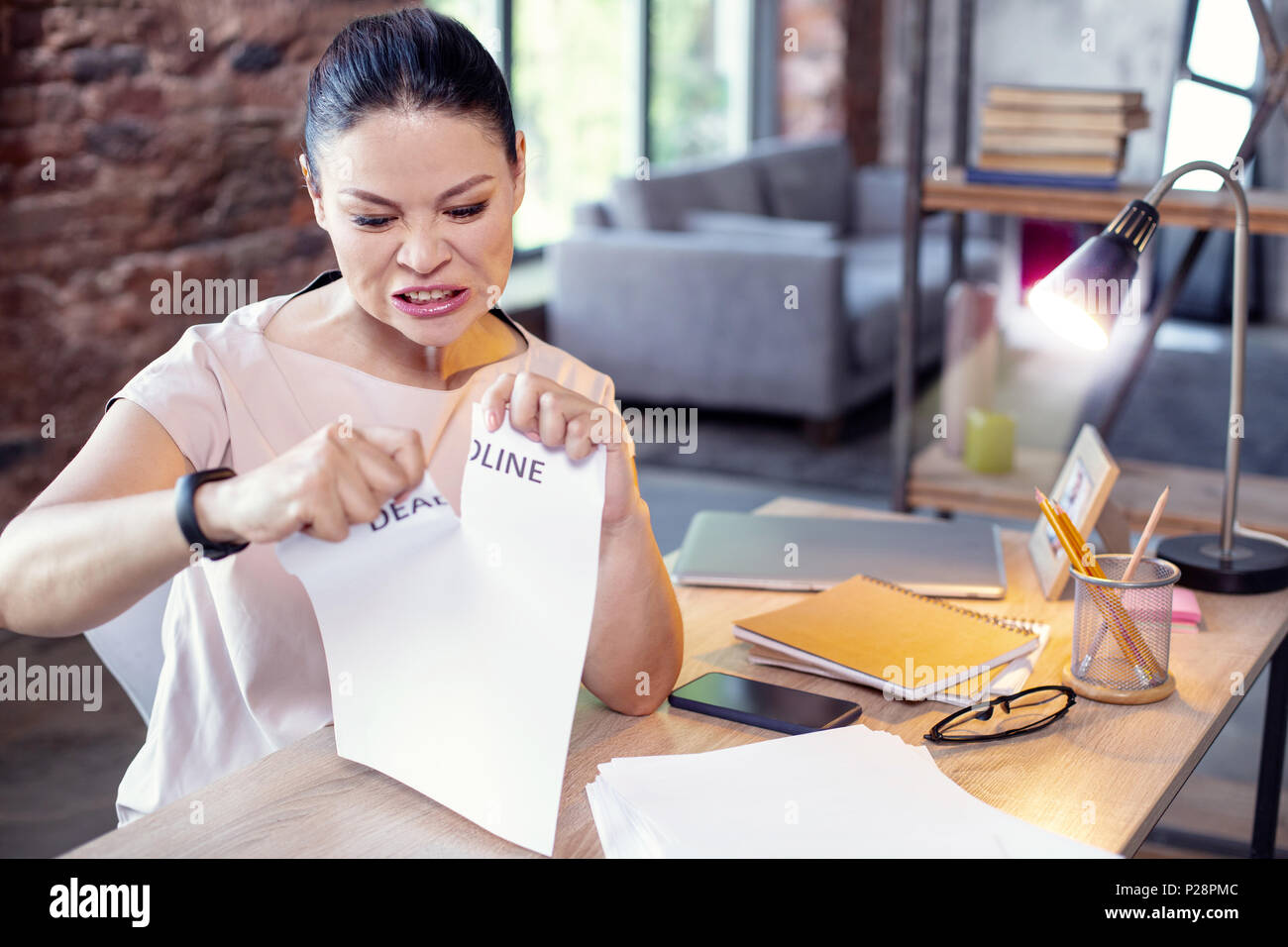 Stressful female employee pulling apart paper - Stock Image