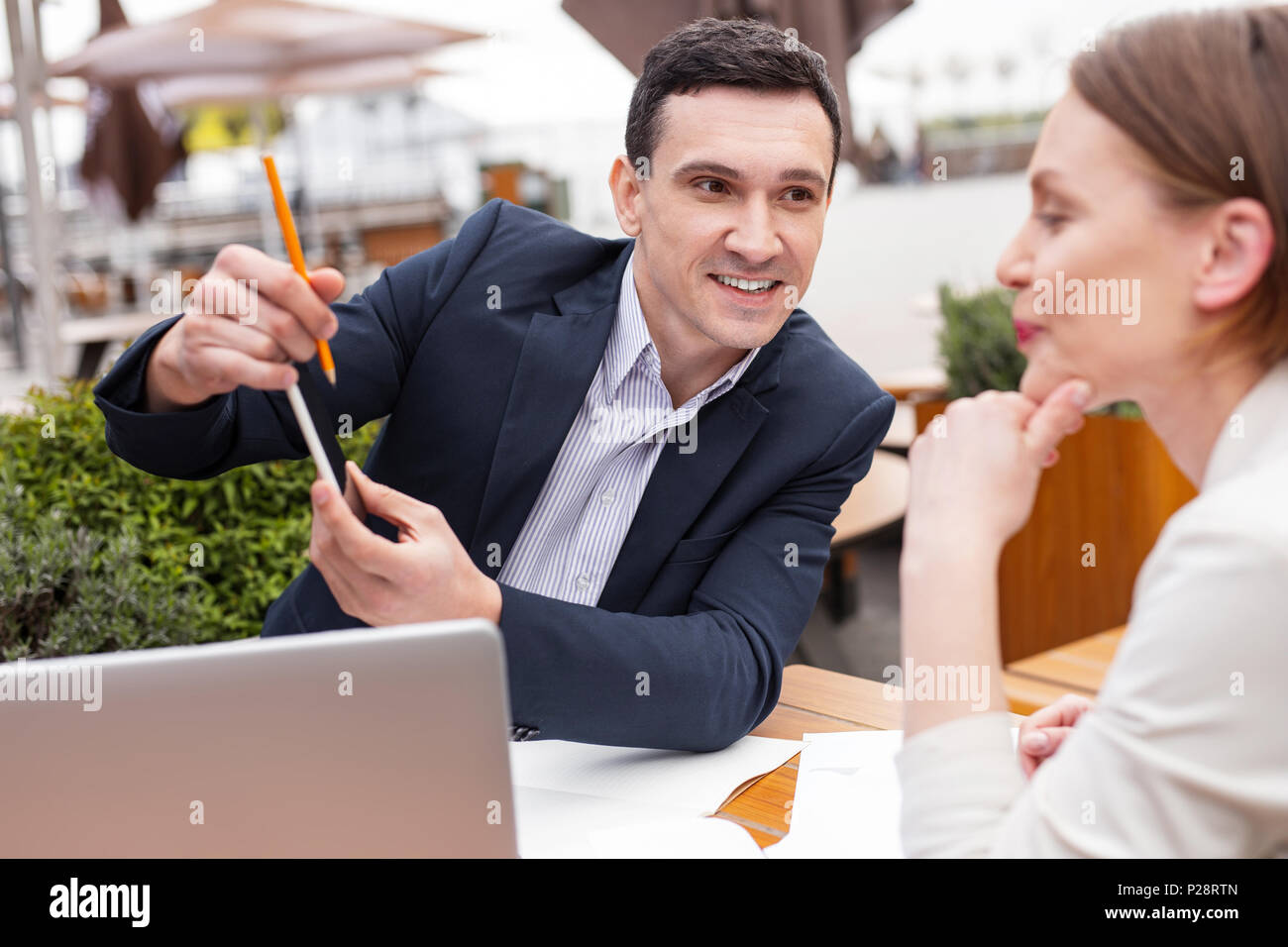 Successful industrious chef explaining work issues - Stock Image
