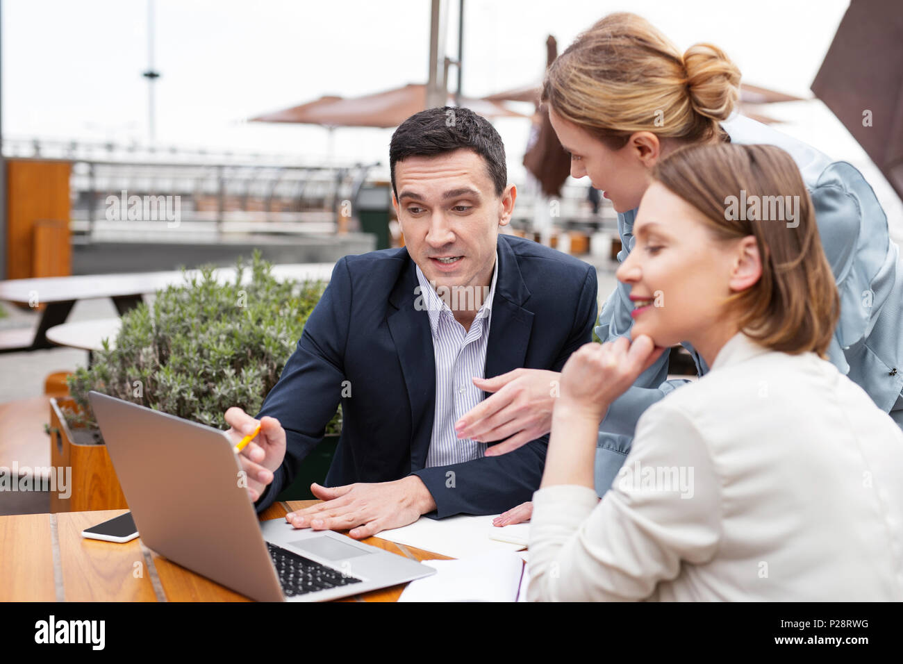 White collar worker explaining actively work plan to his colleagues - Stock Image