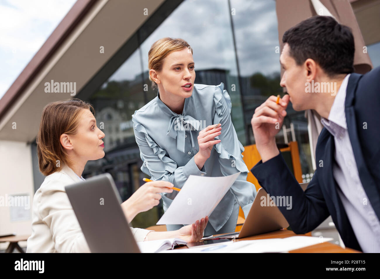 Three prosperous executives feeling employed discussing potential - Stock Image