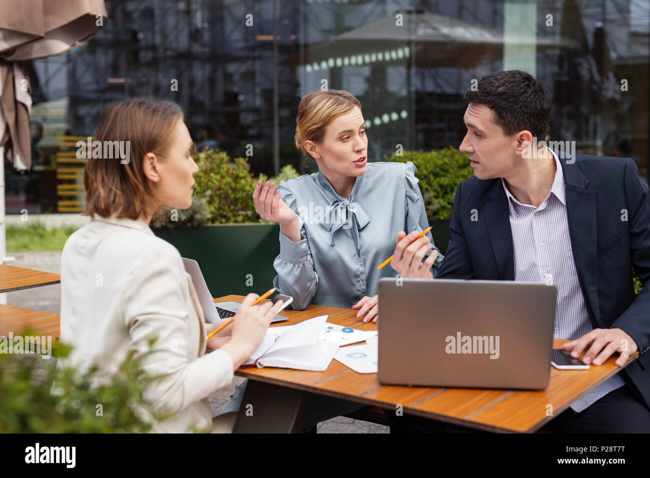 Three managers having dispute about business proposal - Stock Image