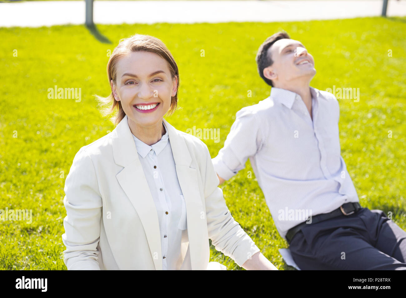 Smiling businesswoman with short haircut smiling broadly - Stock Image