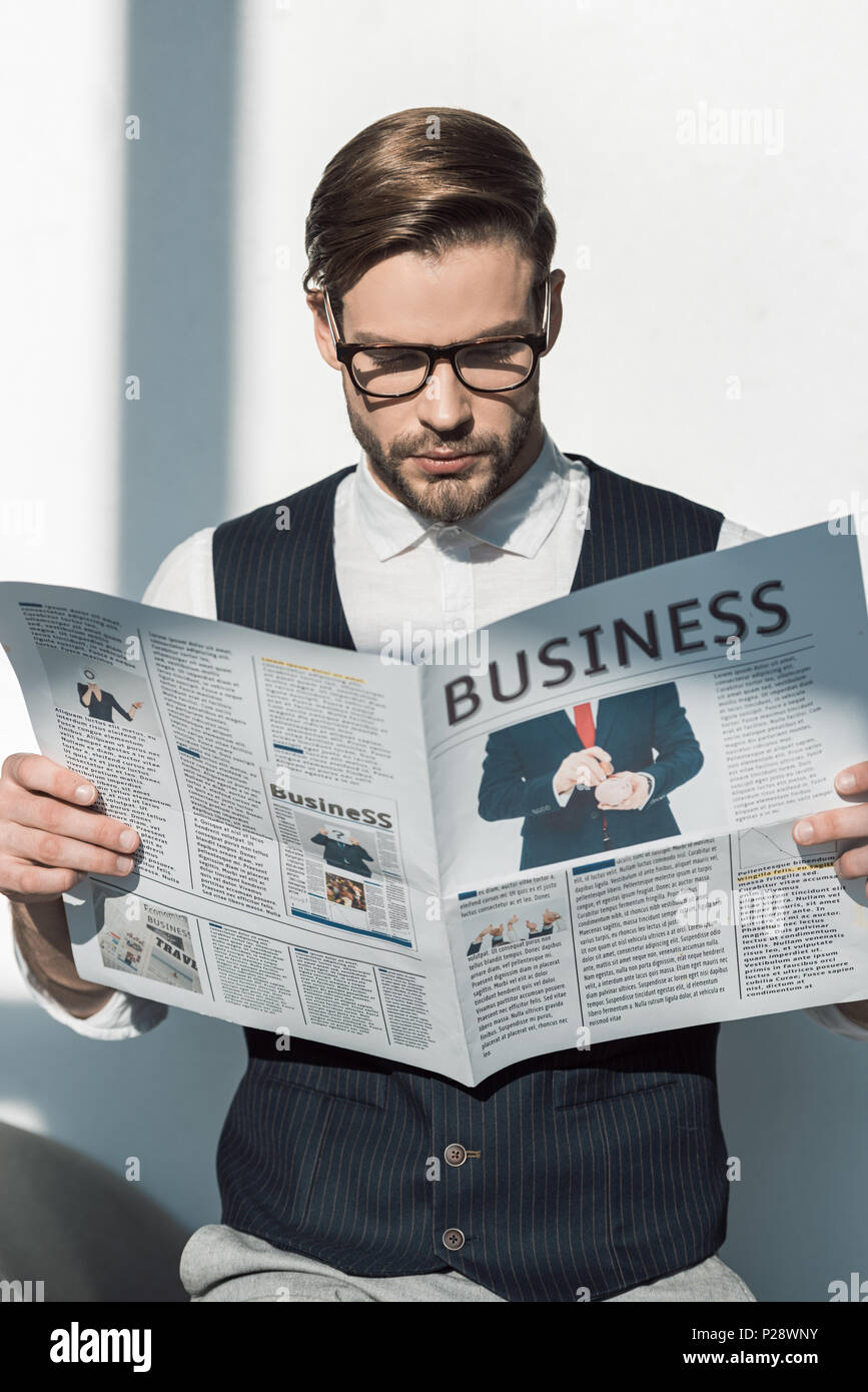 db8cced991 portrait of stylish young businessman in eyeglasses reading newspaper
