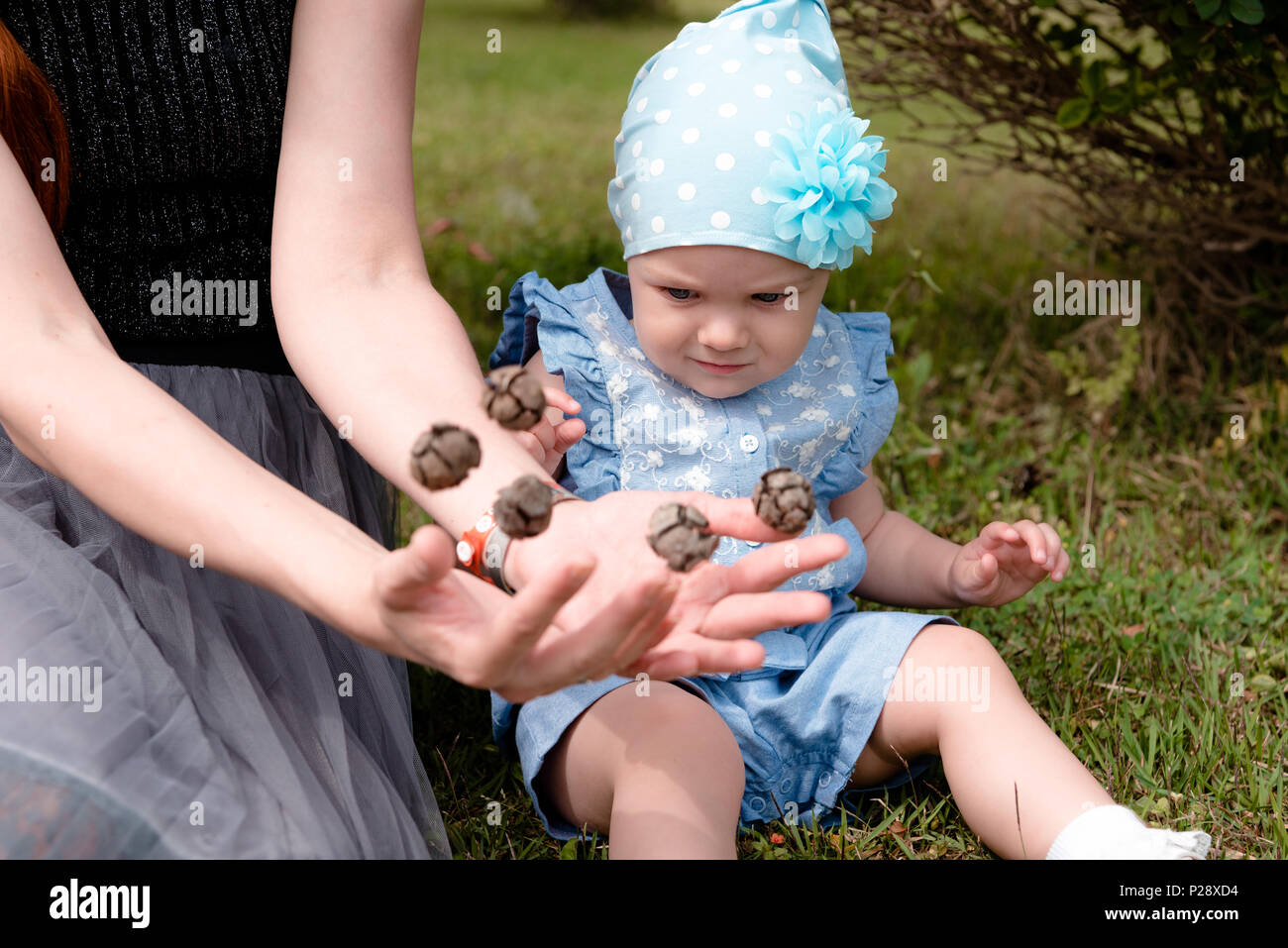the little girl looks at the flying cones in the hands of her mother with distrust. they sit on the grass in the Park. the child has a blue suit and a - Stock Image