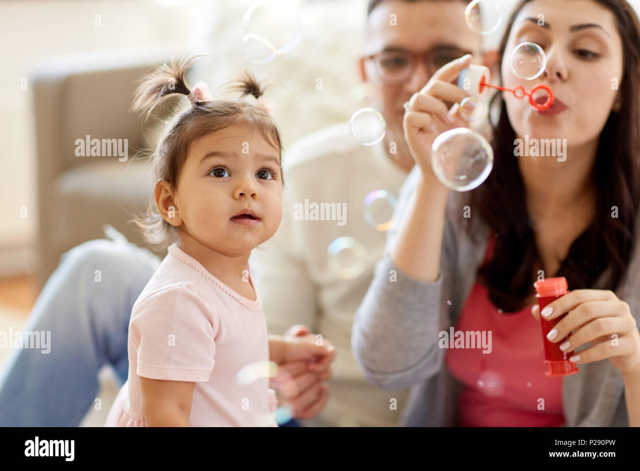 family with soap bubbles playing at home - Stock Image