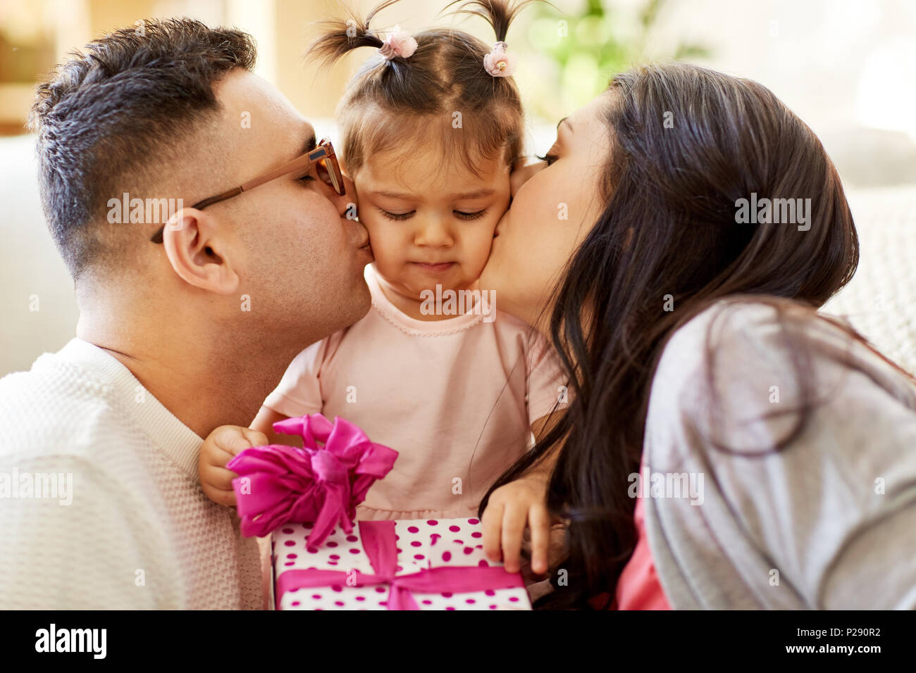 parents kissing little daughter with birthday gift - Stock Image