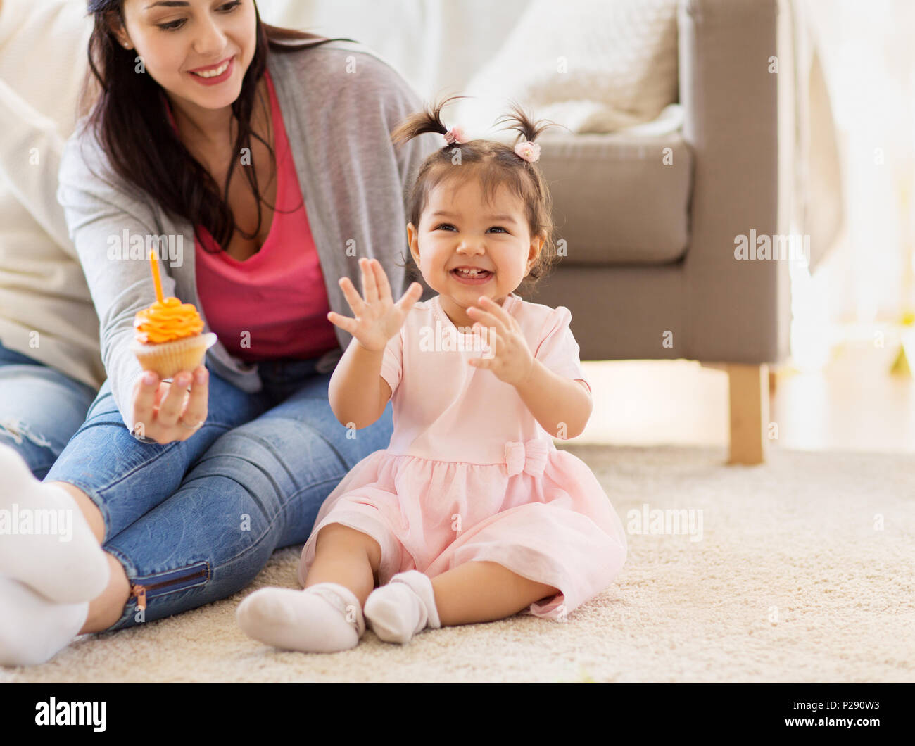 baby girl with mother at home birthday party - Stock Image
