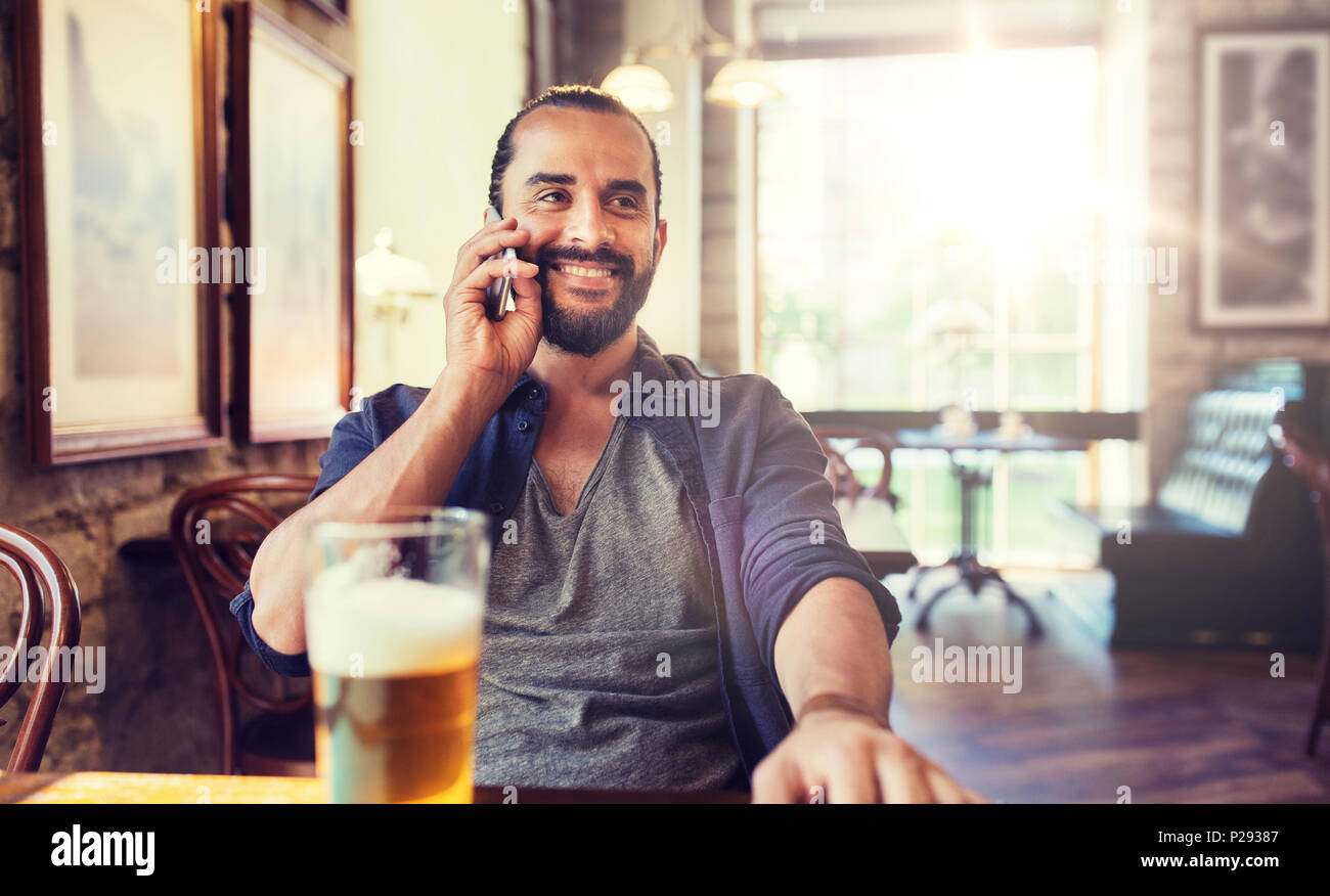 man with smartphone and beer calling at bar or pub - Stock Image