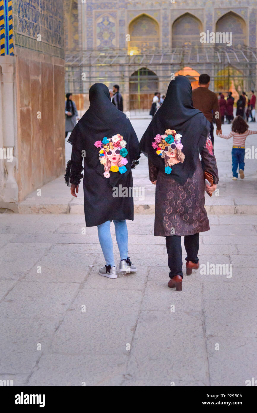 Isfahan, Iran - March 21, 2018: Two girls in black hijab with the same colore pictures of portrait of girls on the street - Stock Image