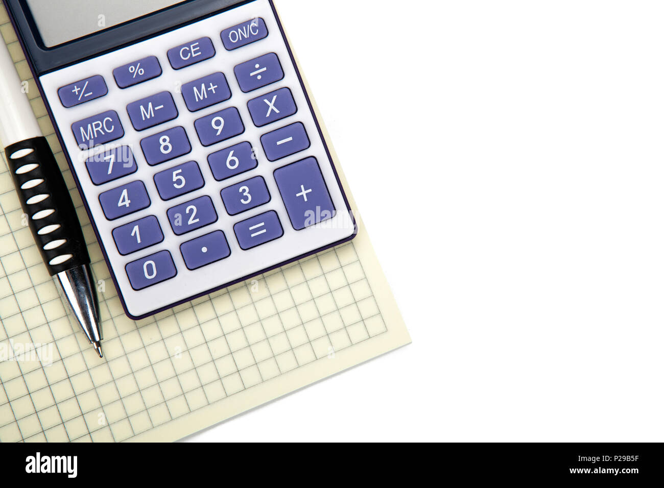 One big calculator with yellow checkbook and stationery on a white table closeup - Stock Image