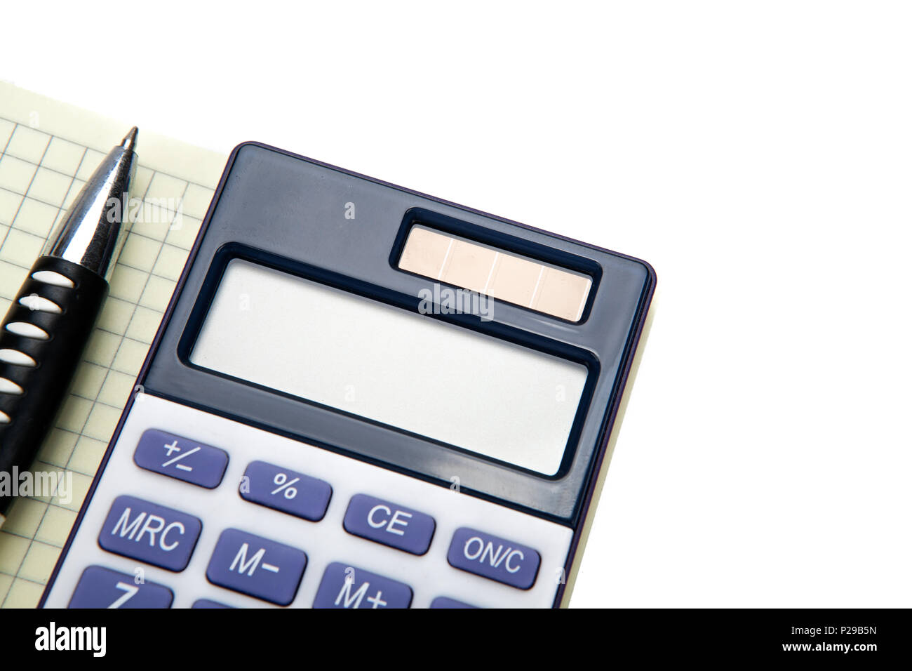 One big calculator and a pen on a white table closeup - Stock Image