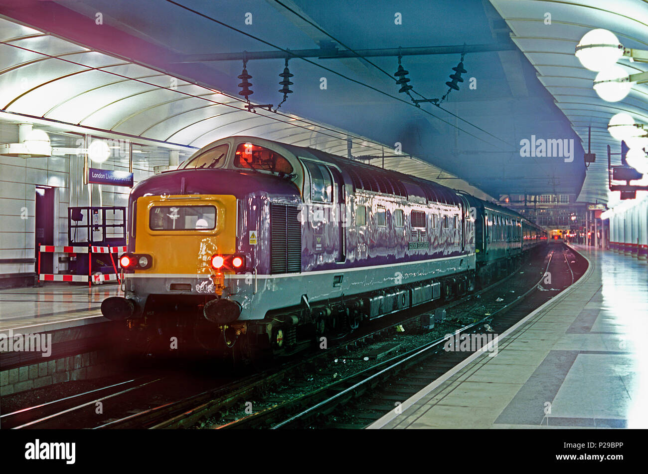"""A class 55 Deltic diesel locomotive number D9016 (55016) """"Gordon Highlander"""" waits for the booked departure time with a Steam Dreams charter. At this time the locomotive was owned by Porterbrook and carried the companies distinctive purple livery. London Liverpool Street. 5th December 2002. Stock Photo"""