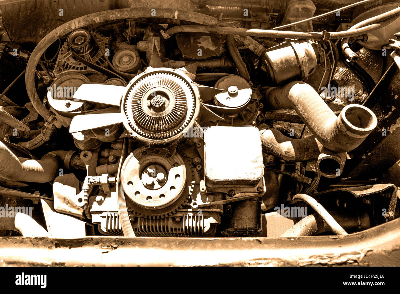 Old broken and dirty car engine close up, view under the hood in sepia tones - Stock Image