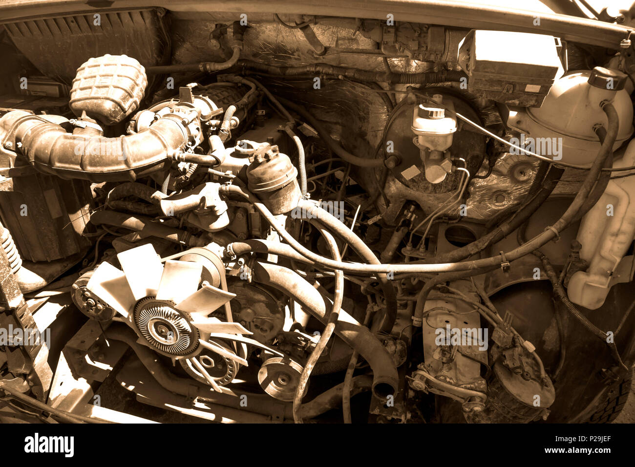 Old broken and dirty car engine close up, view under the hood in sepia tones Stock Photo