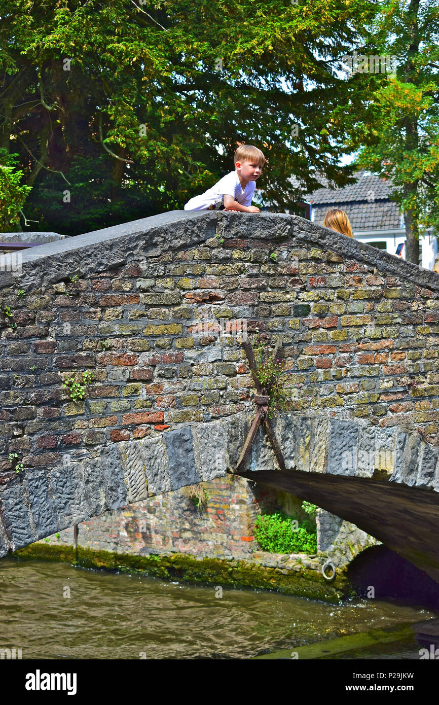 A young boy leans over the edge of the Bonifacius bridge  watching boats pass underneath. Bruges or Brugge, Belgium - Stock Image