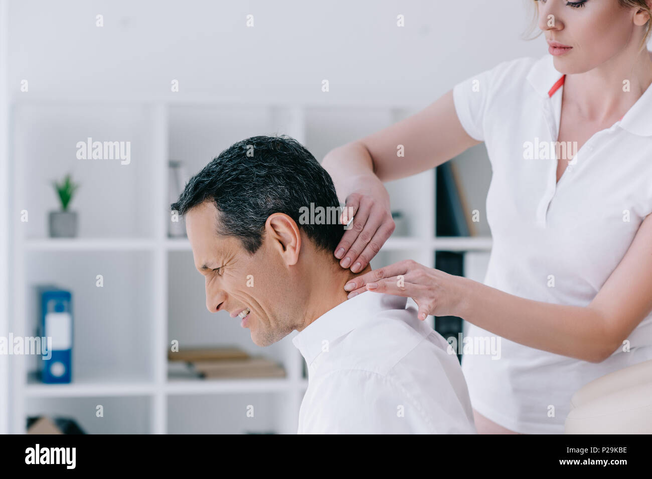 side view of masseuse doing seated neck massage for client at office Stock Photo