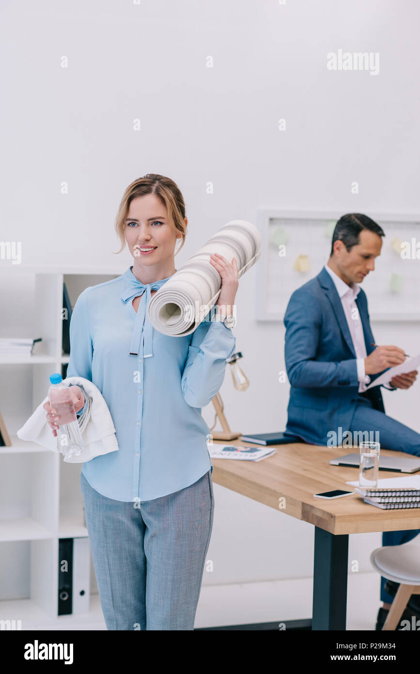 businesswoman with fitness equipment standing at modern office while her colleague working blurred on background - Stock Image
