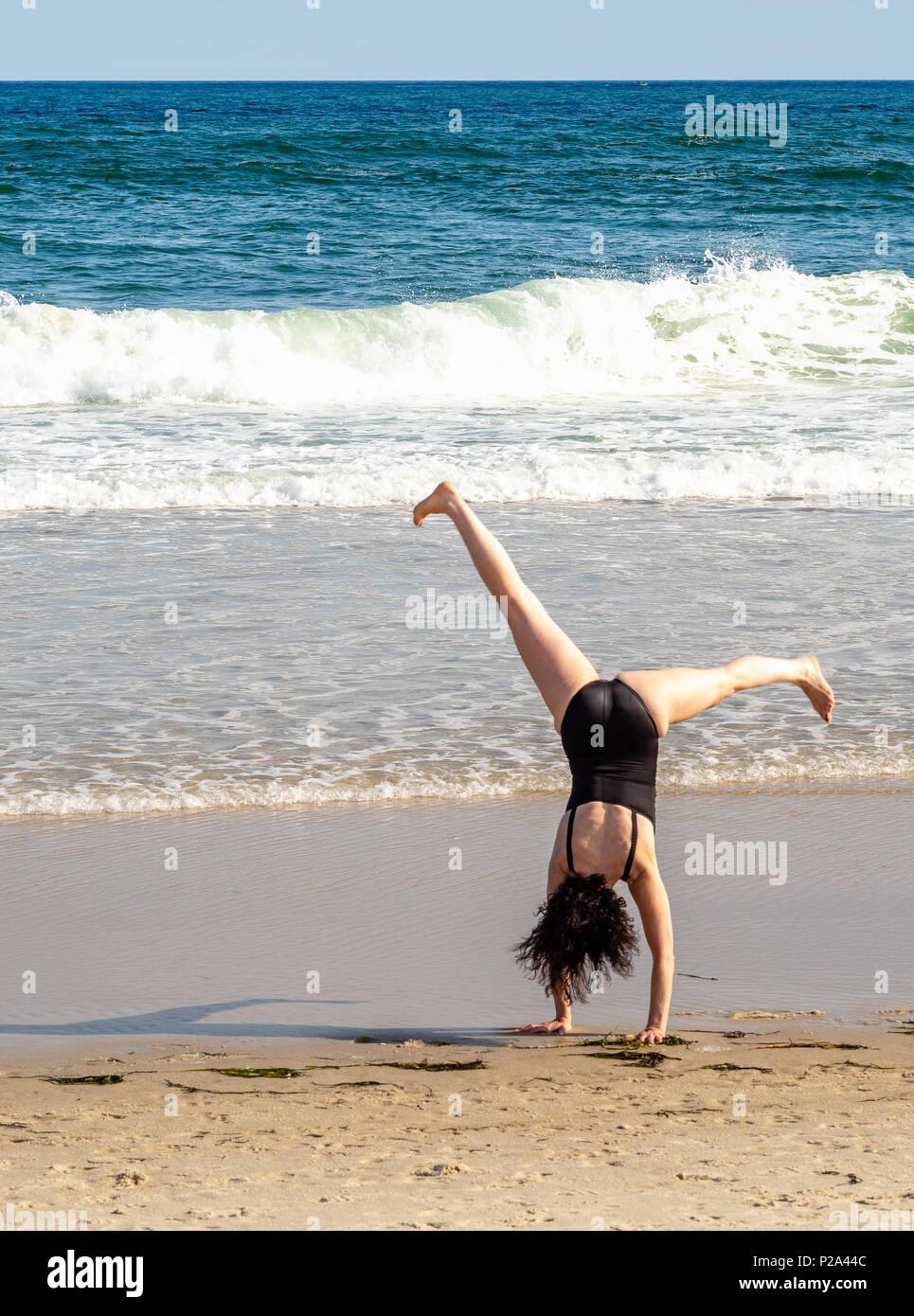 Woman doing cartwheel on beach. - Stock Image
