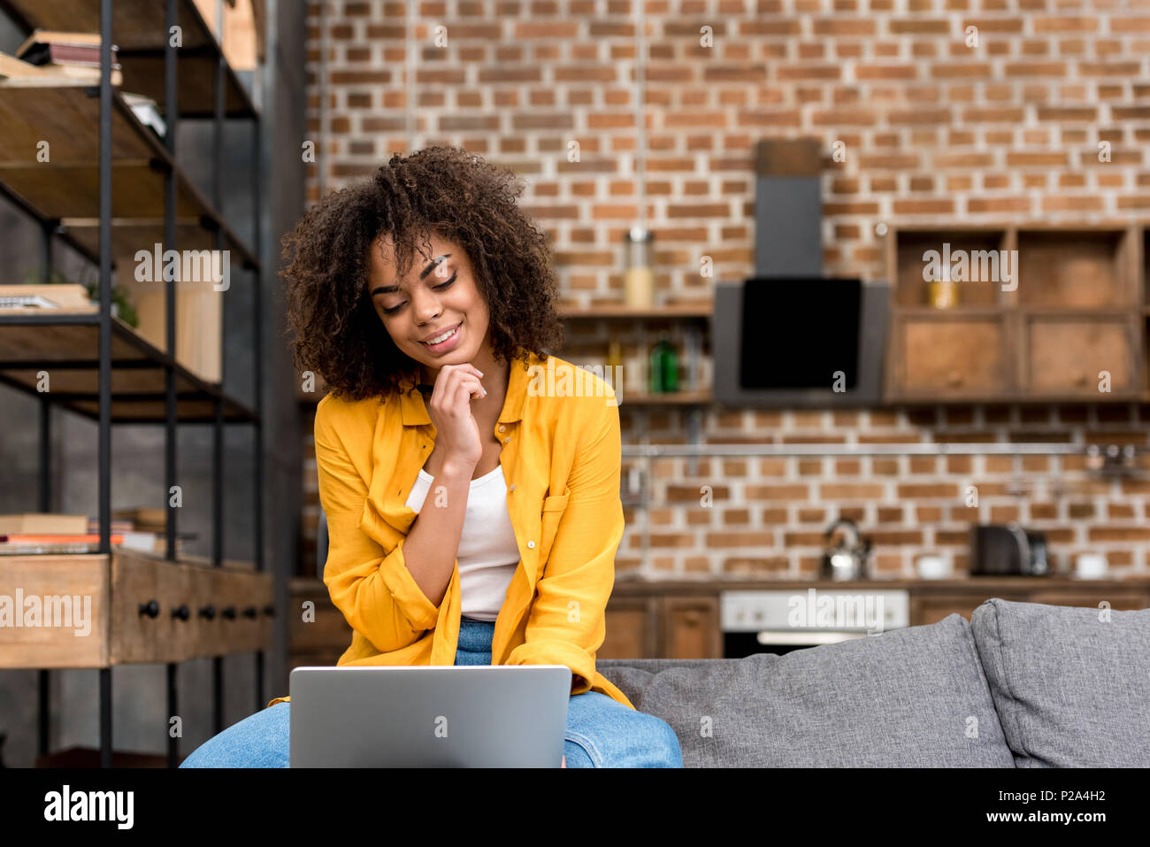 smiling mixed race woman working with laptop at home with blurred loft kitchen on background - Stock Image