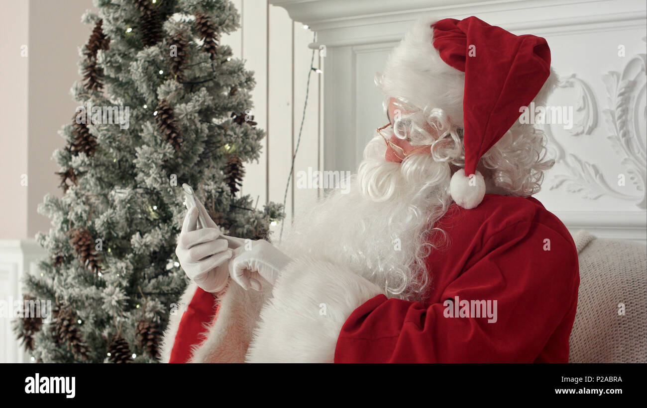 Laughing Santa Claus reading Christmas messages from kids Stock ...