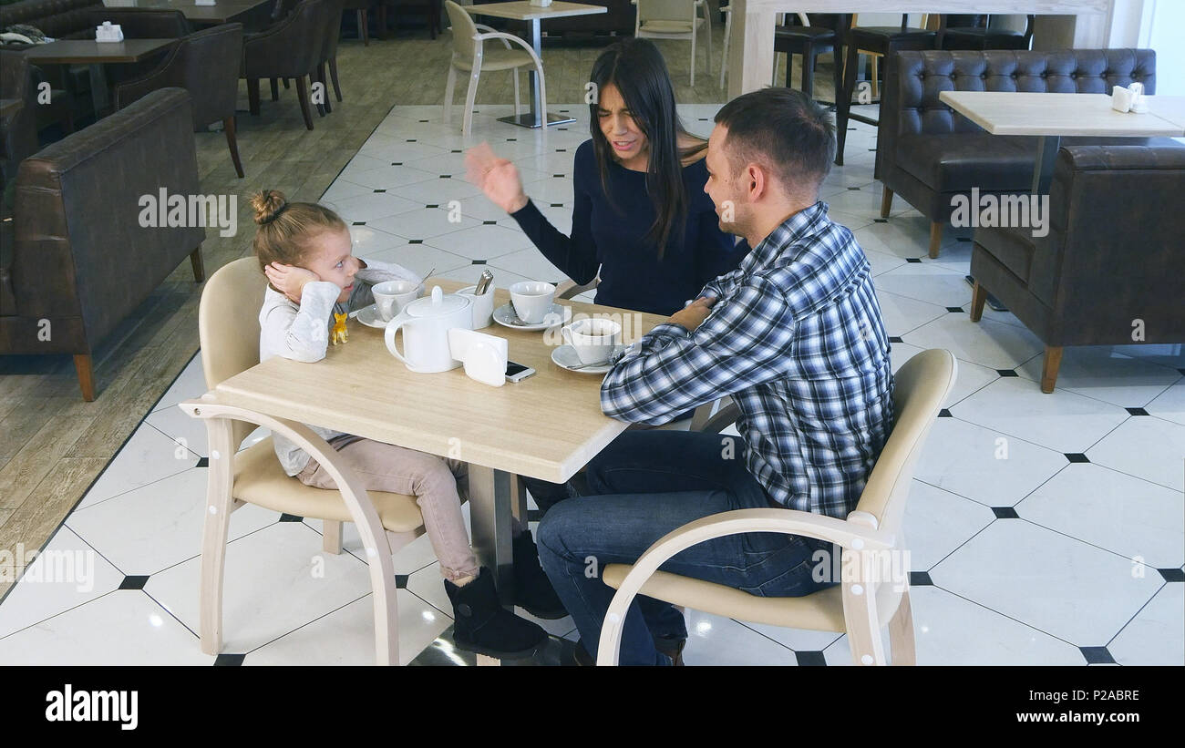 Indignant mother blaming on daughter and husband in cafe. Littke girl closing her ears. - Stock Image
