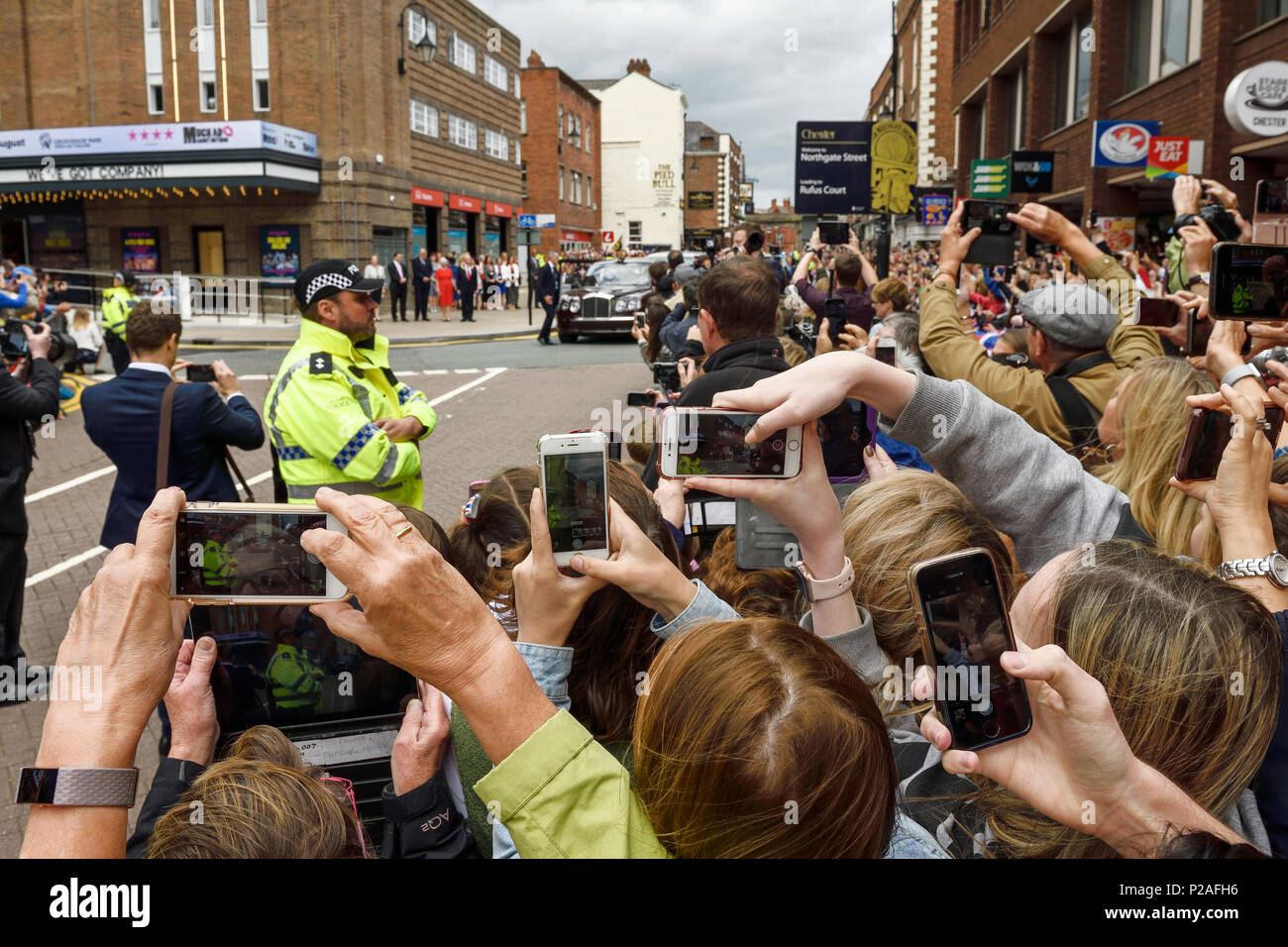 Chester, UK. 14th June 2018. Crowds photograph the arrival of the Queen and the Duchess of Sussex to officially open the Storyhouse theatre, library and arts venue before having lunch in the Town Hall. Credit: Andrew Paterson/Alamy Live News - Stock Image