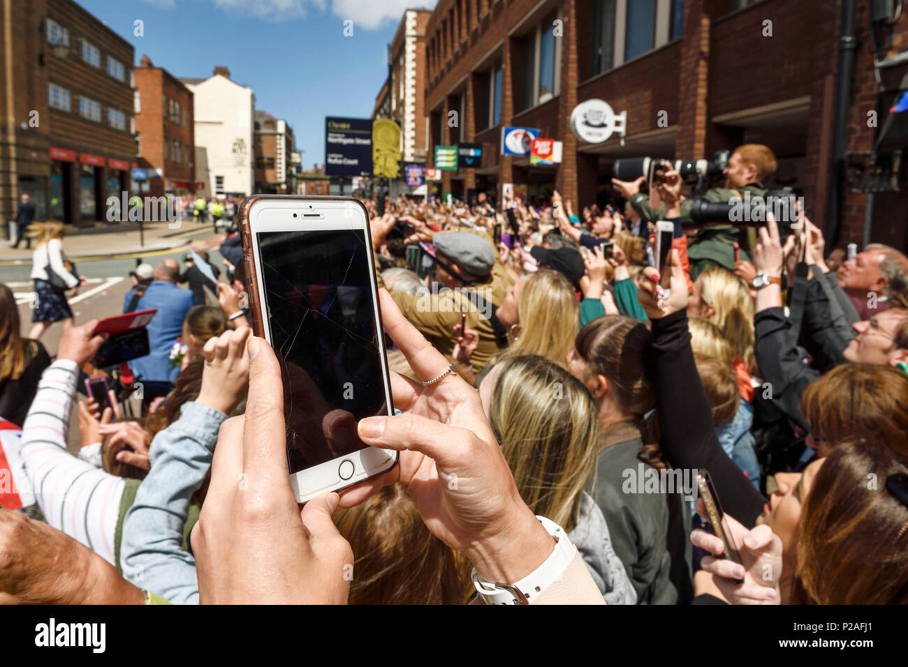Chester, UK. 14th June 2018. Crowds photograph the Queen and the Duchess of Sussex leaving the Storyhouse theatre, library and arts venue before having lunch in the Town Hall. Credit: Andrew Paterson/Alamy Live News - Stock Image