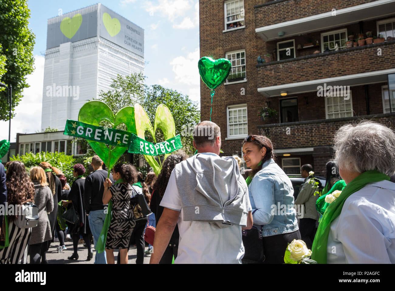 London, UK. 14th June, 2018. Members of the local community, faith leaders, politicians and wellwishers pass the Grenfell Tower, now covered, as they take part in a silent procession from St Helen's Church to the Wall of Truth to mark the first anniversary of the Grenfell Tower Fire. Credit: Mark Kerrison/Alamy Live News - Stock Image