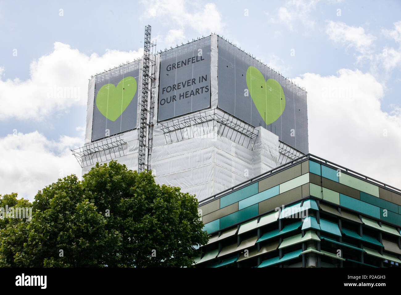 London, UK. 14th June, 2018. Green Grenfell hearts are now positioned at the top of the Grenfell Tower on all sides. Credit: Mark Kerrison/Alamy Live News - Stock Image