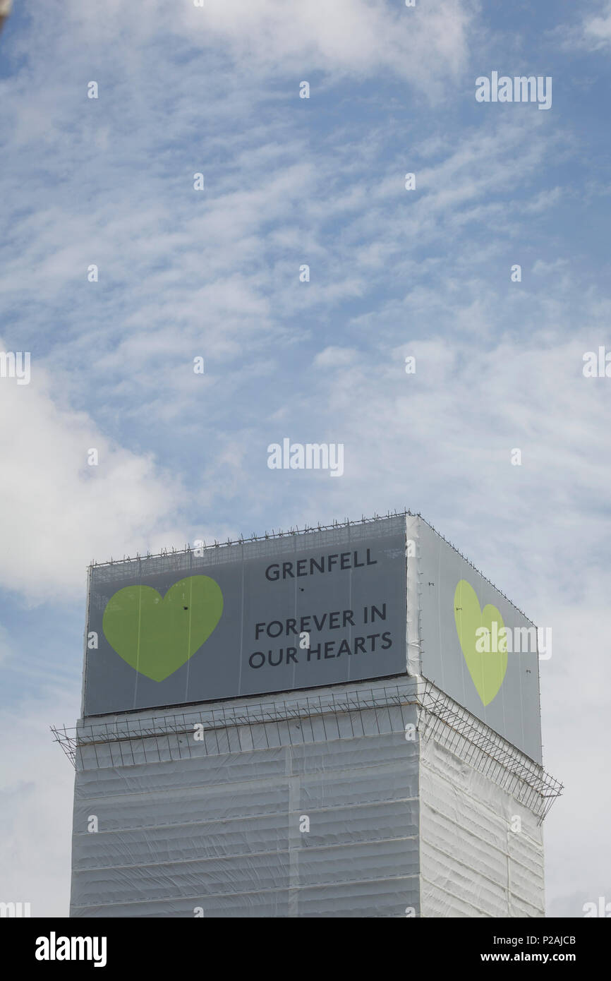 London, UK. 14th Jun, 2018. The covered remains of the Grenfell high-rise Grenfell, on the first anniversary of the tower block disaster. 72 people died when the tower block in the borough of Kensington & Chelsea were killed in what has been called the largest fire since WW2. The 24-storey Grenfell Tower block of public housing flats in North Kensington, West London, United Kingdom. It caused 72 deaths, out of the 293 people in the building, including 2 who escaped and died in hospital. Over 70 were injured and left traumatised. Credit: RichardBaker/Alamy Live News - Stock Image