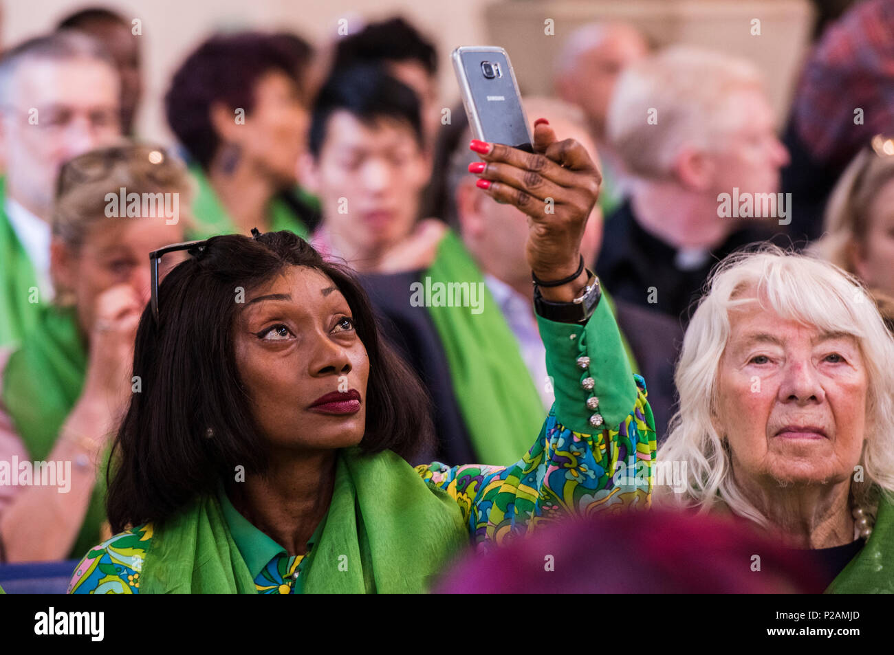 A teary woman holds up her mobile phone while attending the service to mark the Grenfell Fire anniversary in St Helen's Church, North Kensington, London, England, UK, 14th June, 2018s - Stock Image
