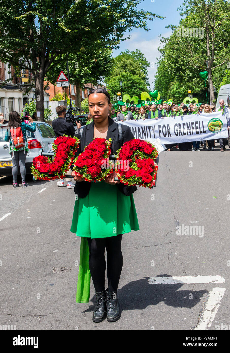 A woman holds a floral tribute saying 'J 4 G' whilst walking towards Grenfell Tower, to mark the one year anniversary of the fire, London, England, UK, 14th June 2018 - Stock Image