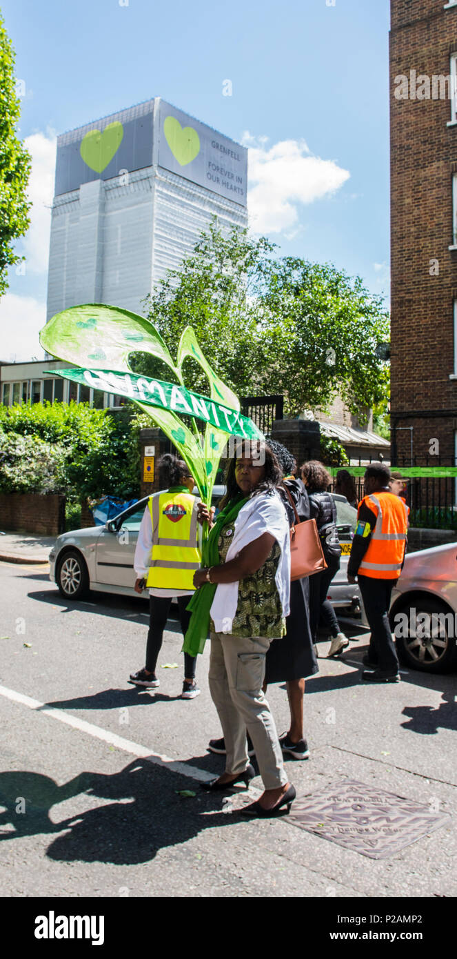 People walking to Grenfell Tower to mark the anniversary of the fire. Clarrie Mendy-Solomon, who lost two family members in the fire, stops and looks at the camera, London, England, UK, 14th June 2018 - Stock Image