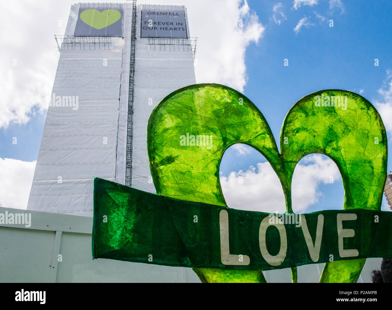 A giant banner with the word Love is left at the base of the Grenfell Tower to mark the anniversary of the fire, London, England, UK, 14th June 2018 - Stock Image