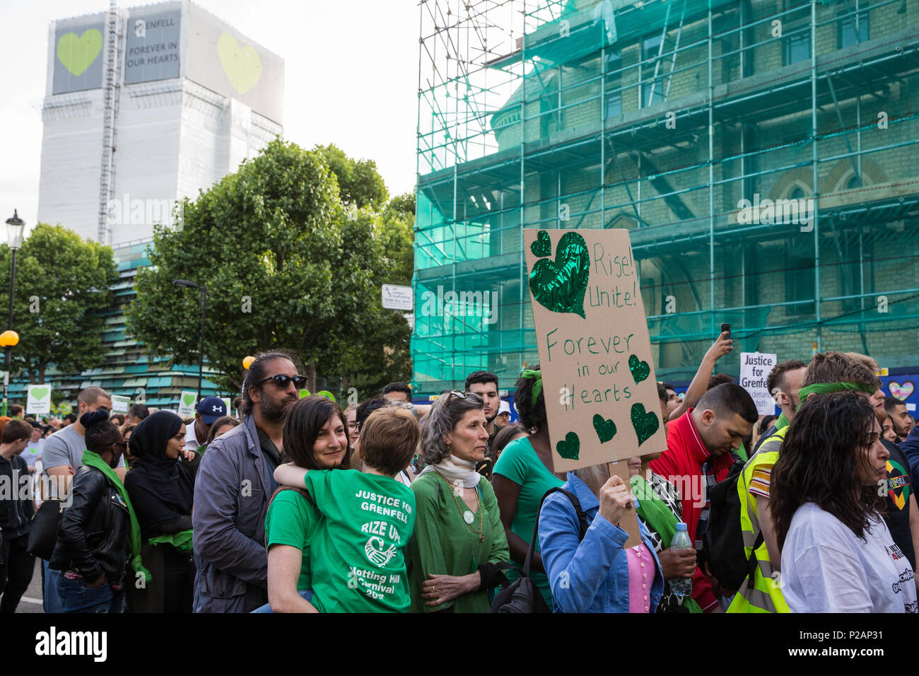 London, UK. 14th June, 2018. Members of the Grenfell community and supporters pass in front of the Grenfell Tower on the Grenfell Silent March through West Kensington on the first anniversary of the Grenfell Tower fire. 72 people died in the Grenfell Tower fire and over 70 were injured. Credit: Mark Kerrison/Alamy Live News - Stock Image