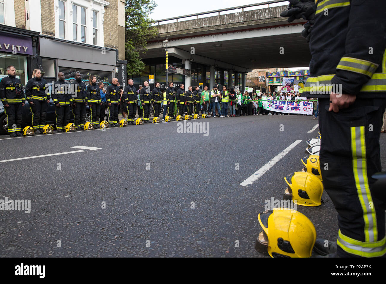 London, UK. 14th June, 2018. A guard of honour prepared by the London Fire Brigade for the Grenfell Silent March through West Kensington on the first anniversary of the Grenfell Tower fire. 72 people died in the Grenfell Tower fire and over 70 were injured. Credit: Mark Kerrison/Alamy Live News - Stock Image