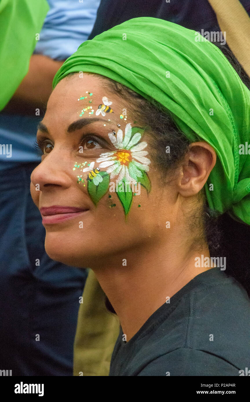 London, UK. 14th June 2018. Some of the thousands who came towalk in silence from close to Grenfell Tower remembering the victims of the disaster on the first anniversary of the disastrous fire which killed 72 and left survivors traumatised had flowers painted on their faces. Many of those made homeless by the fire are still in temporary accomodation a year later despite promises mde by Theresa May and Kensington & Chelsea council, who many fell have failed the local community both before and after the fire. Credit: Peter Marshall/Alamy Live News - Stock Image