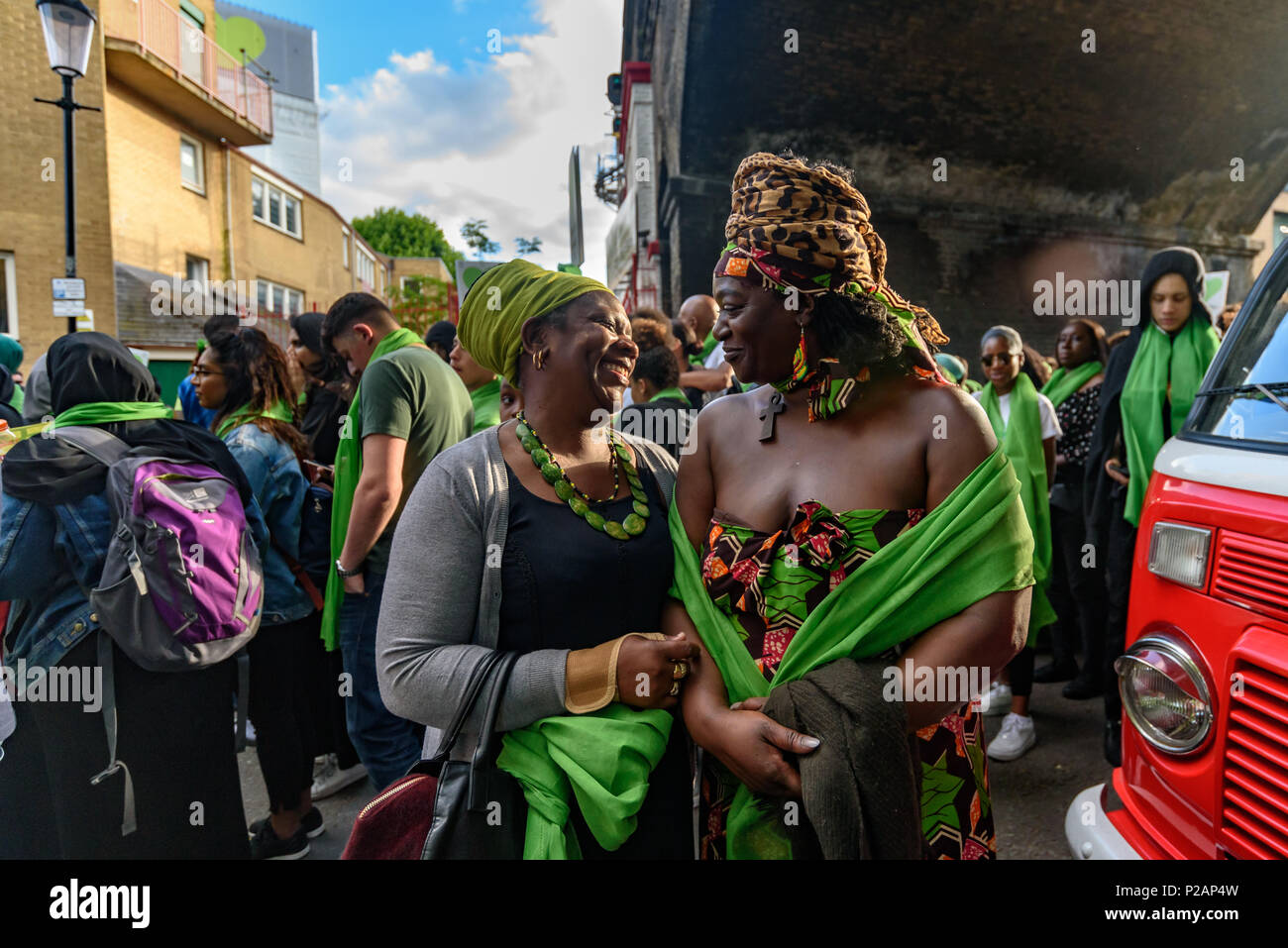 London, UK. 14th June 2018. Two women share a joke as they wait with housands to walk in silence from close to Grenfell Tower remembering the victims of the disaster on the first anniversary of the disastrous fire which killed 72 and left survivors traumatised. Many of those made homeless by the fire are still in temporary accomodation a year later despite promises mde by Theresa May and Kensington & Chelsea council, who many fell have failed the local community both before and after the fire.  call for justic Credit: Peter Marshall/Alamy Live News - Stock Image