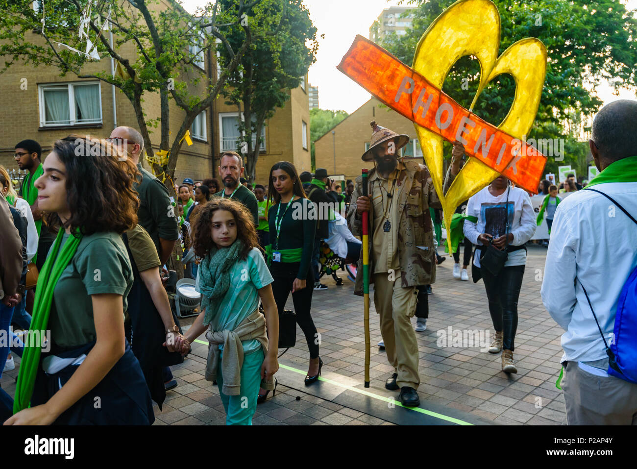 London, UK. 14th June 2018. Notting Hill community organiser Niles Hailstones carries a yellow heart with the message 'Phoenix' on the silent walk from close to Grenfell Tower remembering the victims of the disaster on the first anniversary of the disastrous fire which killed 72 and left survivors traumatised. Many of those made homeless by the fire are still in temporary accomodation a year later despite promises mde by Theresa May and Kensington & Chelsea council, who many fell have failed the local community both before and after the fire. They say had they been listened to and respected Gr - Stock Image