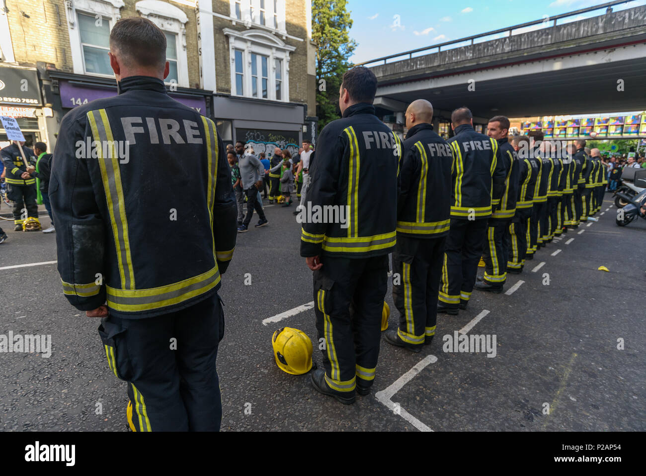 London, UK. 14th June 2018. Firefighters lined both sides of Ladbroke Grove as a guard of honour and are kissed and hugged by many as thousands walk in silence from close to Grenfell Tower remembering the victims of the disaster on the first anniversary of the disastrous fire which killed 72 and left survivors traumatised. Many of those made homeless by the fire are still in temporary accomodation a year later despite promises mde by Theresa May and Kensington & Chelsea council, who many fell have failed the local community both before and after the fire. They say had they been listened to and - Stock Image