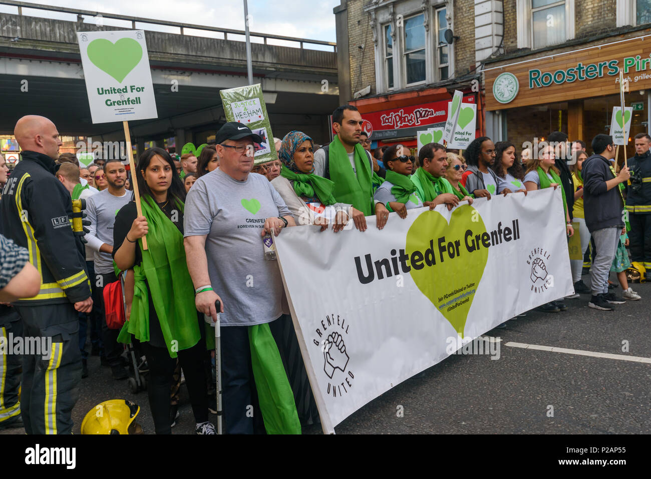 London, UK. 14th June 2018. The 'United for Grenfell' banner at the front of the march halts between the two rows of firefighters froming a guard of honour on Ladbroke Grove. Thousands walked in silence from close to Grenfell Tower remembering the victims of the disaster on the first anniversary of the disastrous fire which killed 72 and left survivors traumatised. Many of those made homeless by the fire are still in temporary accomodation a year later despite promises mde by Theresa May and Kensington & Chelsea council, who many fell have failed the local community both before and after the f - Stock Image