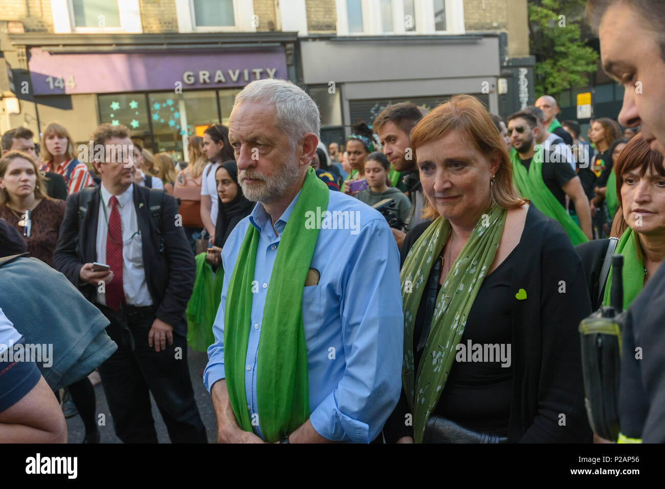 London, UK. 14th June 2018. Labour leader Jeremy Corbyn and local Labour MP Emma Dent Coad wait their turn to shake hands with firefighters at Ladbroke Grove as thousands walk in silence from close to Grenfell Tower remembering the victims of the disaster on the first anniversary of the disastrous fire which killed 72 and left survivors traumatised. Many of those made homeless by the fire are still in temporary accomodation a year later despite promises mde by Theresa May and Kensington & Chelsea council, who many fell have failed the local community both before and after the fire. They say ha - Stock Image