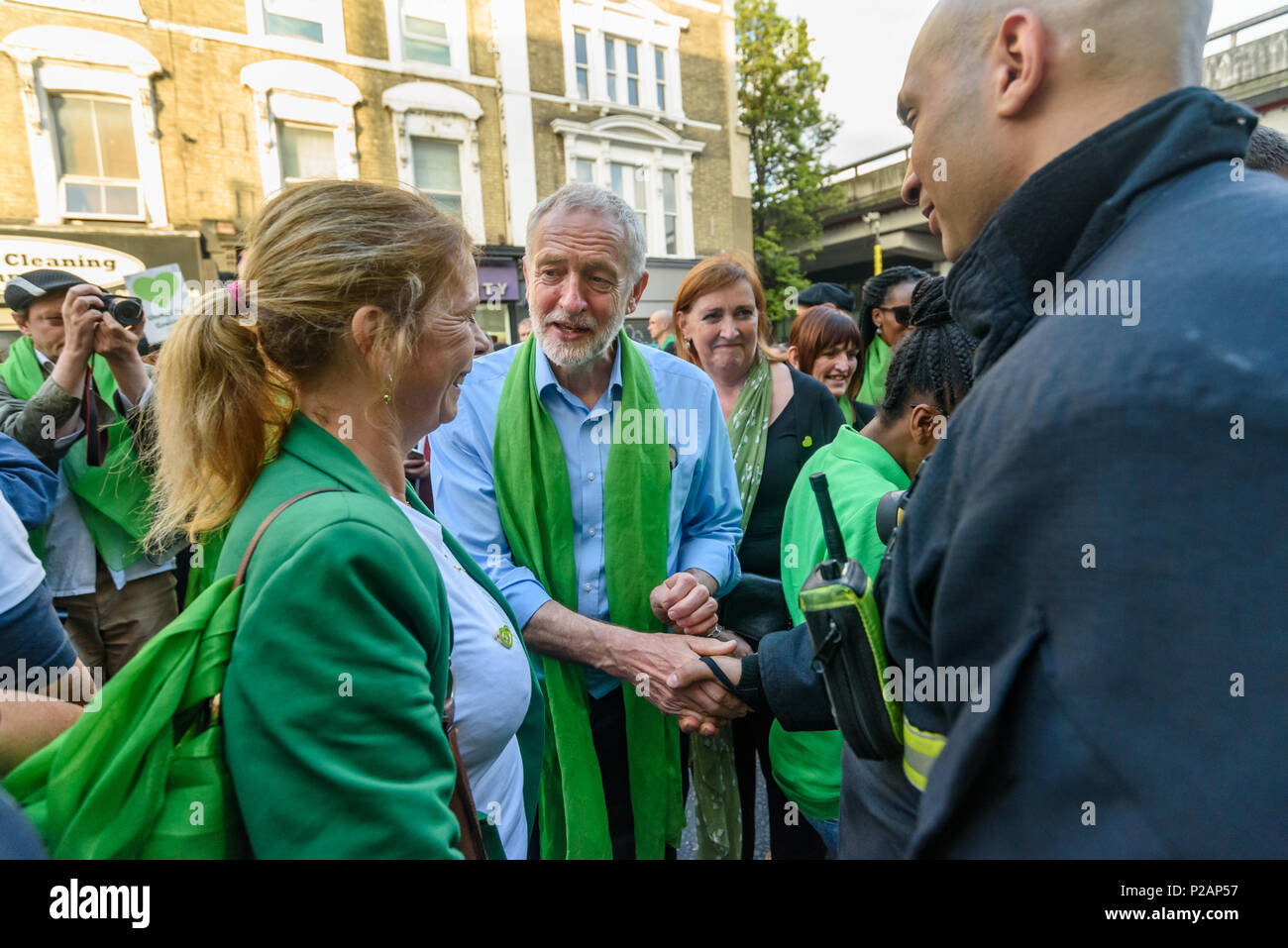 London, UK. 14th June 2018. Labour leader Jeremy Corbyn shakes hands with a firefighter at Ladbroke Grove as thousands walk in silence from close to Grenfell Tower remembering the victims of the disaster on the first anniversary of the disastrous fire which killed 72 and left survivors traumatised. Many of those made homeless by the fire are still in temporary accomodation a year later despite promises mde by Theresa May and Kensington & Chelsea council, who many fell have failed the local community both before and after the fire. They say had they been listened to and respected Grenfell would - Stock Image
