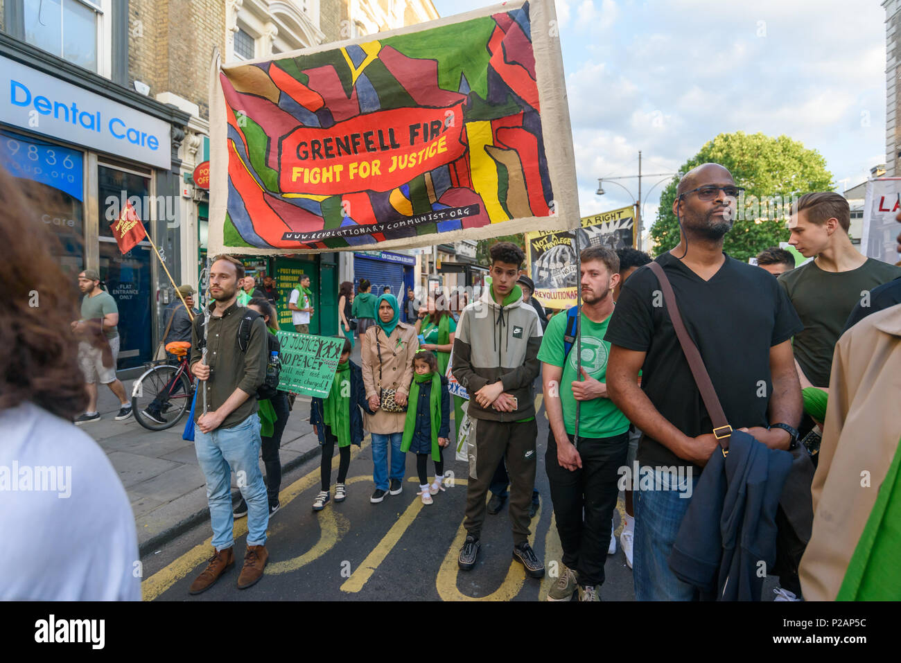 London, UK. 14th June 2018. 'Grenfell Fire - Figth for Justice' reads a banner as thousands walk in silence along Ladbroke Grove remembering the victims of the disaster on the first anniversary of the disastrous fire which killed 72 and left survivors traumatised. Many of those made homeless by the fire are still in temporary accomodation a year later despite promises mde by Theresa May and Kensington & Chelsea council, who many fell have failed the local community both before and after the fire.  call for jus Credit: Peter Marshall/Alamy Live News - Stock Image