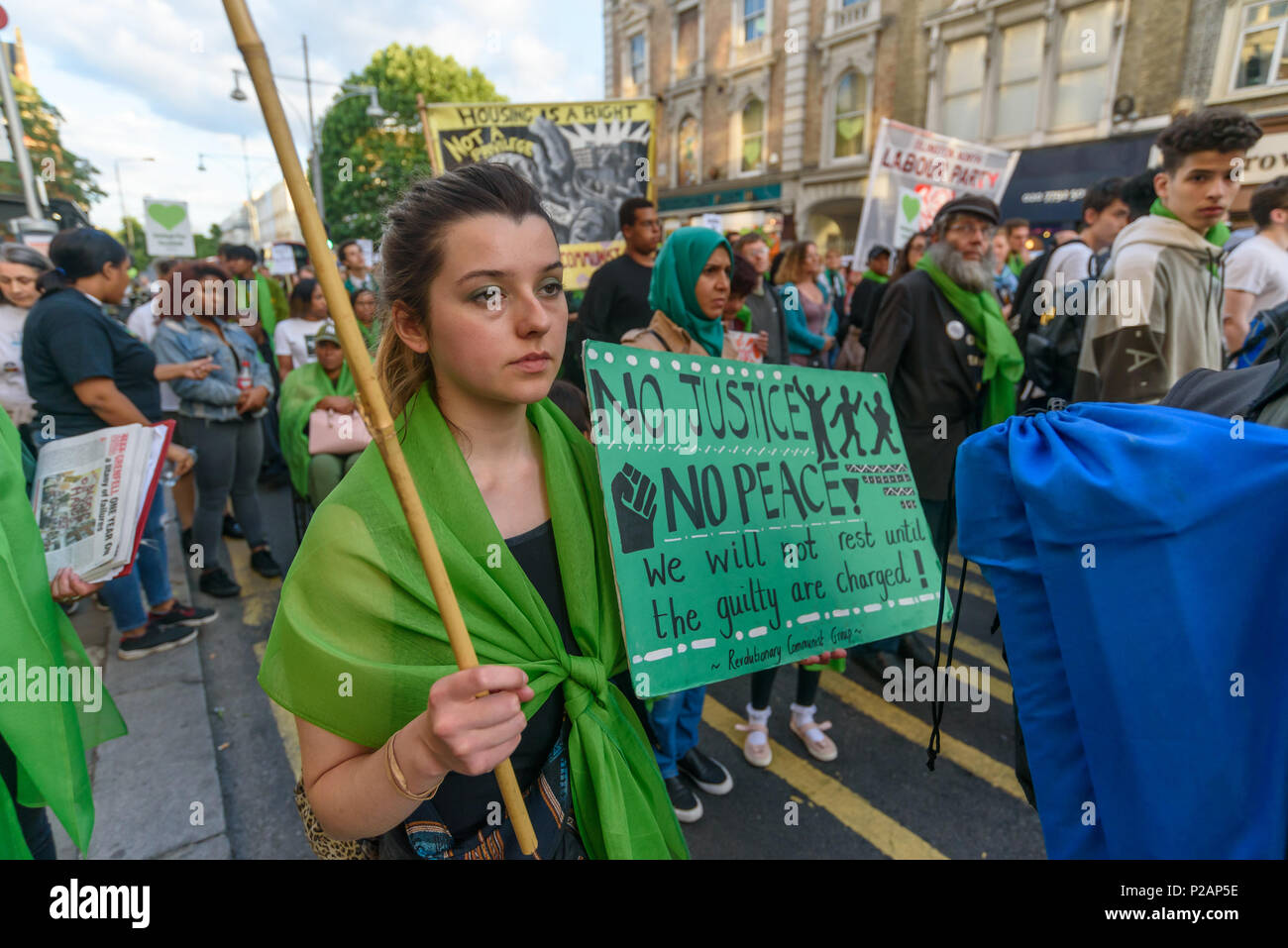 London, UK. 14th June 2018. A woman holds a poster 'No Justice No Peace' as she walks with thousands in silence along Ladbroke Grove remembering the victims of the disaster on the first anniversary of the disastrous fire which killed 72 and left survivors traumatised. Many of those made homeless by the fire are still in temporary accomodation a year later despite promises mde by Theresa May and Kensington & Chelsea council, who many fell have failed the local community both before and after the fire.  call for Credit: Peter Marshall/Alamy Live News - Stock Image