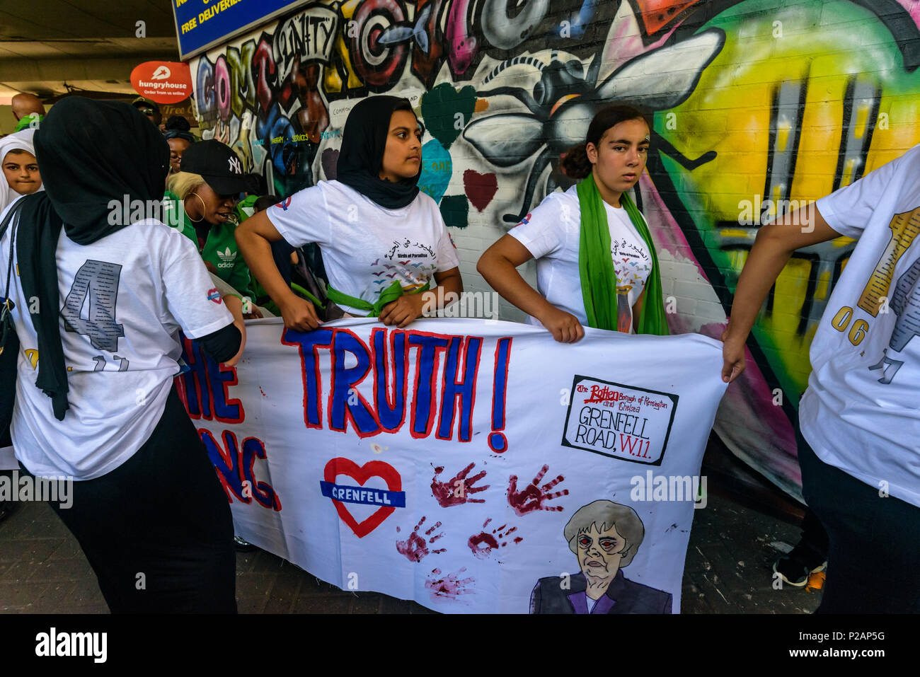 London, UK. 14th June 2018. Grenfell Youth carry their banner under the Westway before thousands walk in silence from close to Grenfell Tower remembering the victims of the disaster on the first anniversary of the disastrous fire which killed 72 and left survivors traumatised. Many of those made homeless by the fire are still in temporary accomodation a year later despite promises mde by Theresa May and Kensington & Chelsea council, who many fell have failed the local community both before and after the fire. Credit: Peter Marshall/Alamy Live News - Stock Image