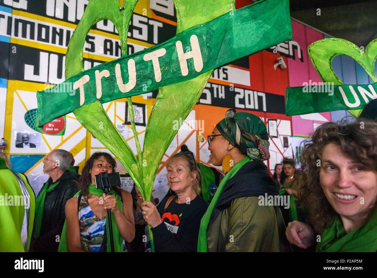 London, UK. 14th June 2018. People hold large Grenfell hearts under the Westway as they wait to walk with thousands in silence from close to Grenfell Tower remembering the victims of the disaster on the first anniversary of the disastrous fire which killed 72 and left survivors traumatised. Many of those made homeless by the fire are still in temporary accomodation a year later despite promises mde by Theresa May and Kensington & Chelsea council, who many fell have failed the local community both before and after the fire. They say had they been listened to and respected Grenfell would not hav - Stock Image