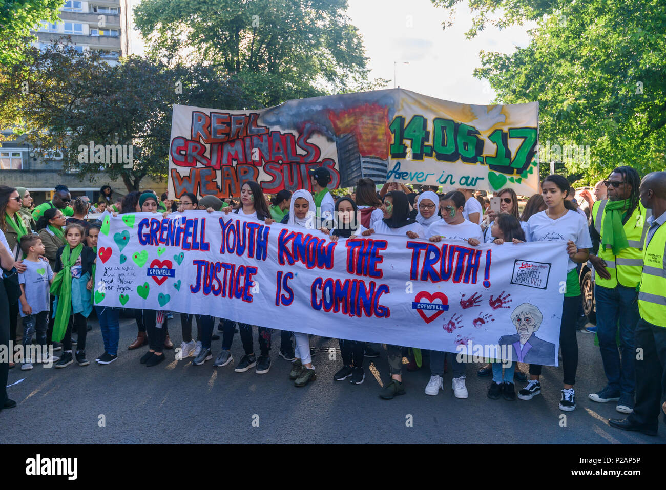 London, UK. 14th June 2018. Grenfell Youth and others line up to walk with their banner with thousands of people in silence from close to Grenfell Tower remembering the victims of the disaster on the first anniversary of the disastrous fire which killed 72 and left survivors traumatised. Many of those made homeless by the fire are still in temporary accomodation a year later despite promises mde by Theresa May and Kensington & Chelsea council, who many fell have failed the local community both before and after the fire. They say had they been listened to and respected Grenfell would not have h - Stock Image
