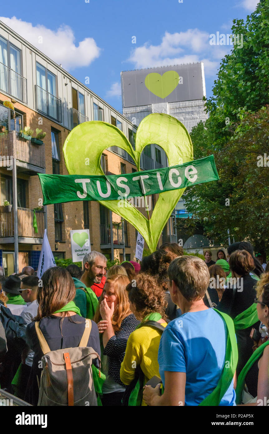 London, UK. 14th June 2018. Grenfell Tower, now covered and with a heart on its top looms over people gathering to walk in silence from close to Grenfell Tower remembering the victims of the disaster on the first anniversary of the disastrous fire which killed 72 and left survivors traumatised. Many of those made homeless by the fire are still in temporary accomodation a year later despite promises mde by Theresa May and Kensington & Chelsea council, who many fell have failed the local community both before and after the fire. They say had they been listened to and respected Grenfell would not - Stock Image