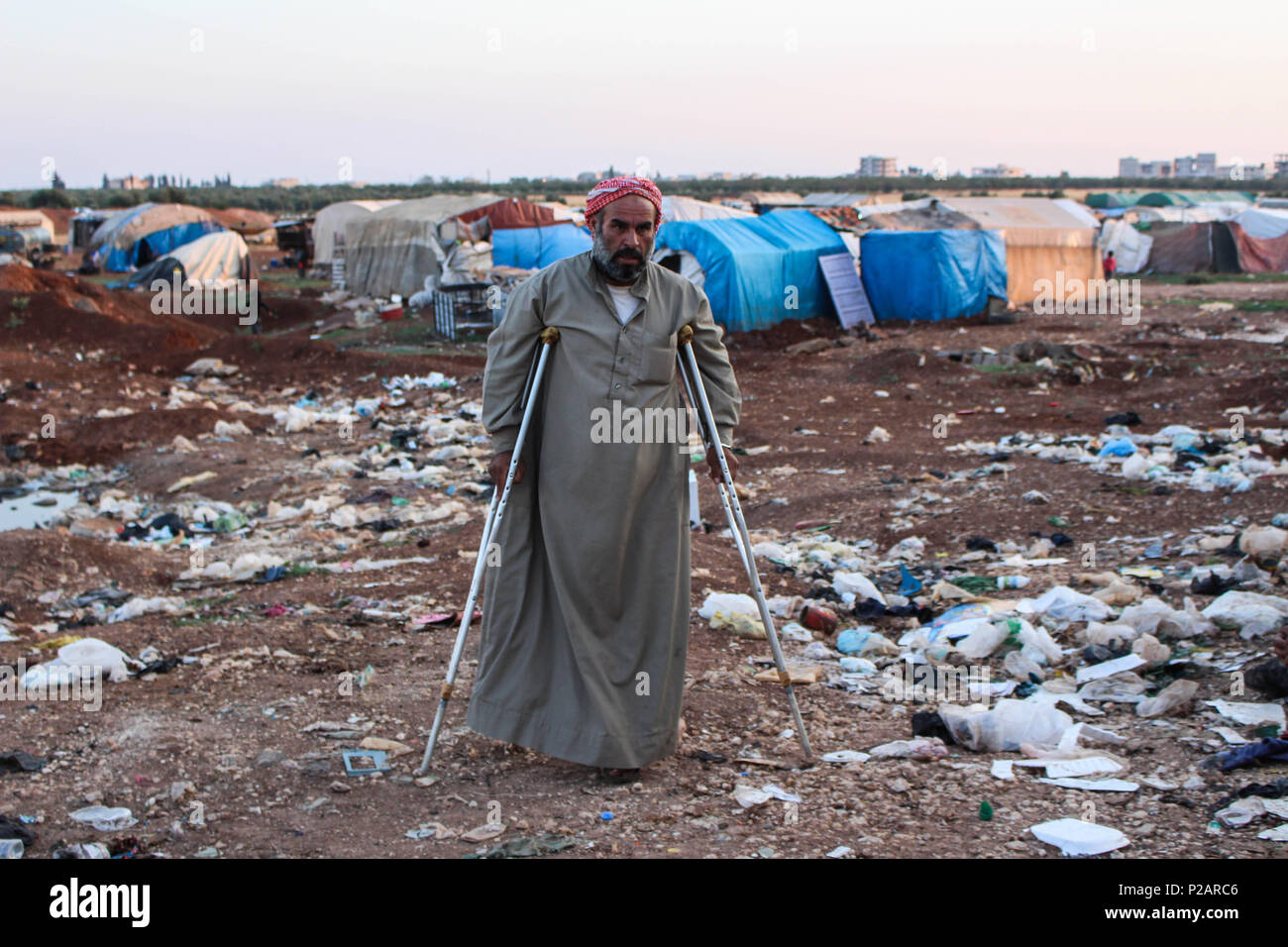 Azaz, Syria. 14th June, 2018. An old man with clutches walking through a dumping area.Eid al-Fitr atmosphere in Al-Tadhamon camp in the countryside of Azaz city where people live displaced from Aleppo city and the countryside. Credit: Muhmmad Al-Najjar/SOPA Images/ZUMA Wire/Alamy Live News - Stock Image